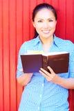 Nätt kvinna för blandat lopp som läser den heliga bibeln royaltyfria bilder