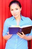 Nätt kvinna för blandat lopp som läser den heliga bibeln arkivfoton