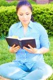 Nätt kvinna för blandat lopp som läser den heliga bibeln arkivbilder