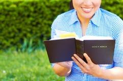 Nätt kvinna för blandat lopp som läser den heliga bibeln fotografering för bildbyråer