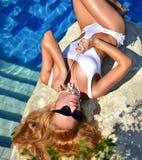 Nätt kvinna för sexigt mode som kopplar av i blå lyxig simbassäng arkivbild
