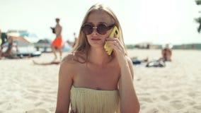 Nätt kvinna i bikini som talar på telefonen på stranden lager videofilmer