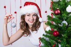 Nätt kvinna i den santa hatten som dekorerar julgranen Arkivbild