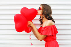 Nätt kvinna i för luftballonger för röd klänning kyssande form för hjärta över vit bakgrund Royaltyfri Bild