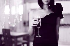 Nätt kvinna i glada trasor som rymmer exponeringsglas av drinken Arkivfoto