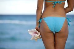 Nätt kvinna i ljus - blå bikini som rymmer ett skal fotografering för bildbyråer