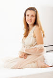 Nätt kvinna i nightrobesammanträde i säng Fotografering för Bildbyråer
