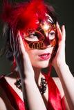 Nätt kvinna, i röd maskering och att se för klänninginnehav royaltyfria foton