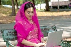 Nätt kvinna i rosa indisk kläder med bärbar dator. fotografering för bildbyråer