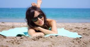 Nätt kvinna i solglasögon som solbadar på en strand Royaltyfria Foton