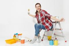 Nätt kvinna i tillfällig kläder som sitter på stege med borsten, instrument för renoveringlägenheten som isoleras på vit arkivbilder