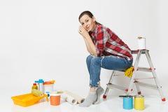 Nätt kvinna i tillfällig kläder som sitter på stege med instrument för renoveringlägenhetrum som isoleras på vit royaltyfri fotografi