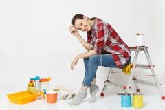 Nätt kvinna i tillfällig kläder som sitter på stege med instrument för renoveringlägenhetrum som isoleras på vit arkivfoto