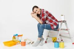 Nätt kvinna i tillfällig kläder som sitter på stege med instrument för renoveringlägenhetrum som isoleras på vit fotografering för bildbyråer
