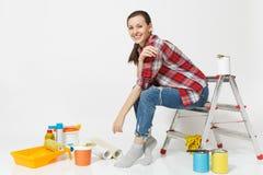 Nätt kvinna i tillfällig kläder som sitter på stege med instrument för renoveringlägenhetrum som isoleras på vit arkivbilder