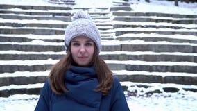 Nätt kvinna i vinterhattleenden som står som är utvändiga på det insnöat skogen med snöig trappabakgrund Stående av a lager videofilmer