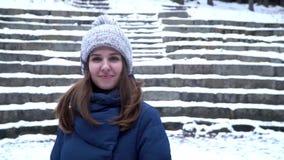 Nätt kvinna i vinterhattleenden som står som är utvändiga på det insnöat skogen med snöig trappabakgrund Stående av a stock video