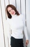 Nätt kvinna i vit poloneck på plankväggen Arkivbilder