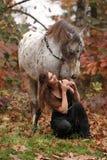 Nätt kvinna med appaloosahästen i höst Royaltyfri Foto