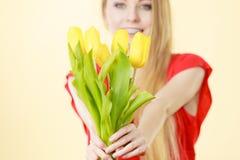 Nätt kvinna med den gula tulpangruppen Arkivfoton