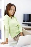 Nätt kvinna med den hemmastadda bärbara datorn royaltyfri foto