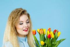 Nätt kvinna med den röda gula tulpangruppen Arkivbild