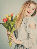 Nätt kvinna med den röda gula tulpangruppen Arkivfoto
