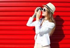 Nätt kvinna med den retro kameran som skjuter upp över rött Arkivfoto