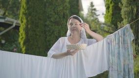 Nätt kvinna med den vita sjalen på hennes huvud som äter körsbär som ser kameran som utomhus ler över klädstrecket stock video