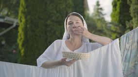 Nätt kvinna med den vita sjalen på hennes huvud som äter körsbär som ser kameran som utomhus ler över klädstrecket arkivfilmer
