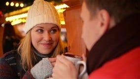 Nätt kvinna med den vitt hatten och Grey Mitts Having Hot Drink och samtal med den stiliga mannen Lyckliga par i varm kläder arkivfilmer