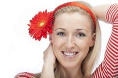 Nätt kvinna med en röd tusensköna i hennes hår royaltyfri fotografi