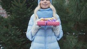 Nätt kvinna med gåvor på denträd bakgrunden stock video