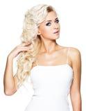 Nätt kvinna med långa blonda lockiga hår Arkivfoto