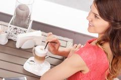 Nätt kvinna med latte i kafeteria Royaltyfri Fotografi