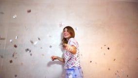 Nätt kvinna med leendet som poserar på kameran som står på bakgrund av den ljusa väggen arkivfilmer