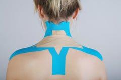 Nätt kvinna med sportar som tejpar på kroppen arkivfoto