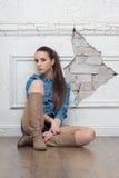 Nätt kvinna med tillfällig stil på den gamla väggen Royaltyfri Fotografi