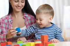 Nätt kvinna och hennes sonbarn som spelar med byggnadskvarter royaltyfria bilder