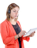 Nätt kvinna på hörluren och innehav en minnestavlaPC royaltyfria foton