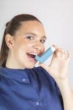 Nätt kvinna, sjuksköterska, genom att använda astmainhalatorn Arkivbild