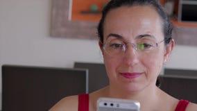 Nätt kvinna som är hemmastadd med den smarta telefonmobilen lager videofilmer