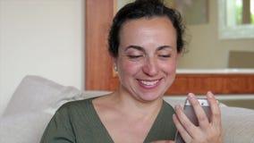 Nätt kvinna som är hemmastadd med den smarta telefonmobilen stock video