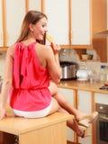 Nätt kvinna som äter den stickande pepparkakakakan Royaltyfri Bild