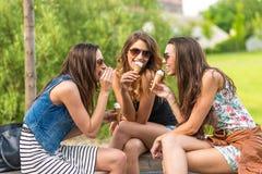 nätt kvinna som 3 äter glass i stad och att sitta på en bänk som skrattar Royaltyfri Fotografi