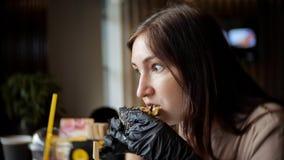 Nätt kvinna som äter snabbmathamburgaren på kafét royaltyfri fotografi