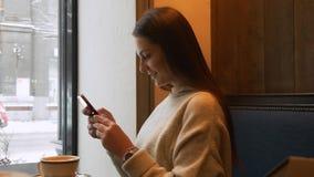 Nätt kvinna som använder app på smartphonen i kafét som dricker kaffe stock video