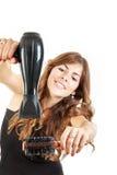 Nätt kvinna som använder hårtork och hårborsten på arbete Royaltyfri Fotografi
