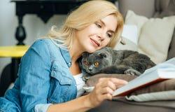 Nätt kvinna som daltar hennes katt Fotografering för Bildbyråer