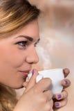 Nätt kvinna som dricker kaffe arkivbild